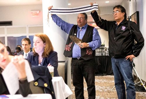 Band Councillors from the Chippewas of the Thames First Nation hold aloft a Two Row Wampum Belt